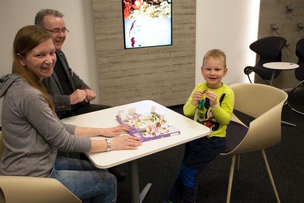 Der vierjährige Domenik freut sich zusammen mit seiner Mutter Desiree G. und Mario Geithe vom Internatsdienst des BFW Leipzig über die Schokoladenkuh aus dem Weihnachtskalender. © M. Lindner, BFW Leipzig